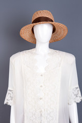 Elegant straw hat on female mannequin. Dummy wearing white silk blouse and brown hat, grey background.