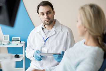 Confident man in white gown and gloves having talk to woman working in dentistry cabinet.