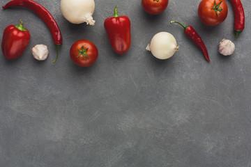 Border of fresh vegetables on grey background