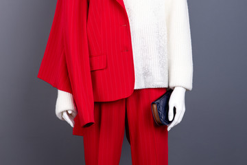 Female mannequin with wallet, cropped image. Red elegant suit and white knitted sweater on female mannequin close up. Ladies fashion clothes and accessories.