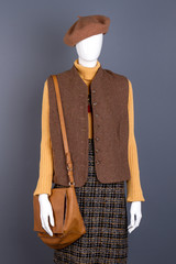 Mannequin in casual women outfit. Brown beret, waistcoat and handbag on mannequin, grey background. Feminine elegance and style.