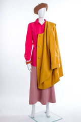 Female mannequin with yellow coat. Beret, blouse, skirt and overcoat. Women fashion look.