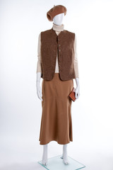 Brown beret, waistcoat and skirt. Female mannequin dressed in vest and skirt, white background. Female clothes and accessories.