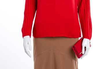 Close up red women sweater and wallet. Warm pullover and skirt for women. Women clothes and accessories.