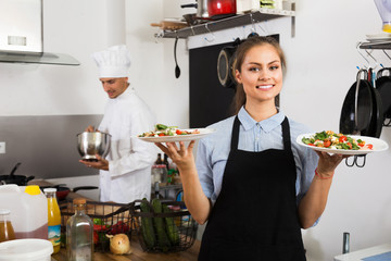 young waitress with served salad on kitchen.