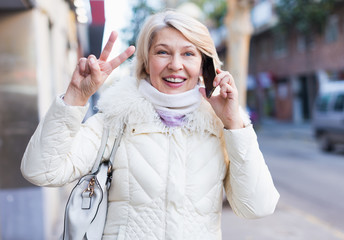 Smiling mature female is walking and talking by phone