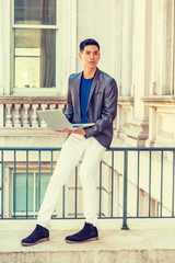 Young Asian American Man studying, working in New York, wearing gray blazer, white pants, black shoes, sitting on railing on vintage office building, working on laptop computer. Filtered effect..