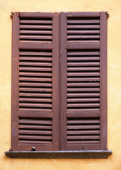 Italy. An antique closed window with wooden shutters in the city of Como.