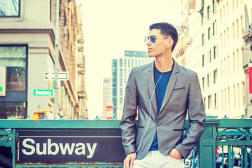 Young Asian American Man traveling in New York, dressing in gray blazer, white pants, wearing sunglasses, earphones, listening music, standing on street by Subway sign, waiting..