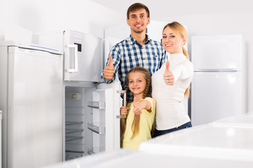 Positive family with child choosing refrigerator