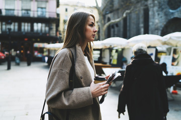 Office worker female in casual clothes going to the office with a take away coffee cup and a newspaper after lunch. Hipster girl holding coffee cup and new magazine while crossing the street.