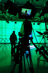 Silhouette of a digital video camera in front of a green screen.