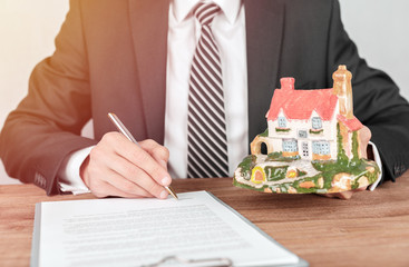 Businessman signs contract behind home architectural model. Real estate concept.