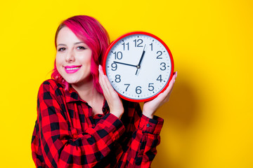 Young redhead girl with big clock. Portrait isolated on yellow background