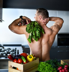 muscular sport man standing on kitchen with groceries vegetables hold radish in hands looking at the corner smiling