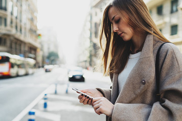 Portrait of beautiful designer girl looking at mobile phone while chatting online on a blurred urban background. Stylish hipster girl reading messages on smartphone while crossing the road