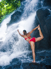 young happy and attractive woman doing yoga exercise posing under beautiful tropical waterfall getting wet smiling happy in meditaton
