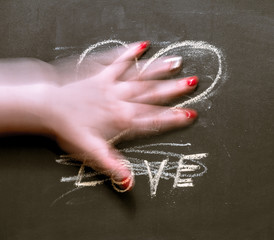 """On the chalkboard written """"Love"""" and painted heart. The female hand erases the inscription."""