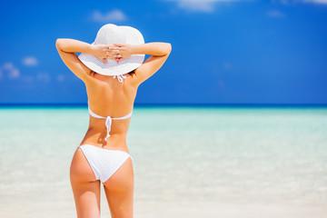 Back of young woman in bikini standing on the beach