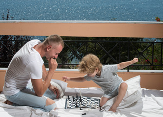 Child play chess with father. child and father on balcony with sea view.