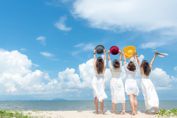 Smiling group woman wearing fashion white dress summer walking on the sandy ocean beach, beautiful blue sky background.  Happy woman enjoy and relax vacation. Lifestyle and Travel Concept