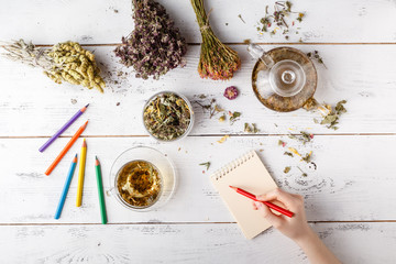 Bunch of medicinal herbs, cup of healthy tea and bag of dry healthy coneflowers on wooden board. Herbal medicine.