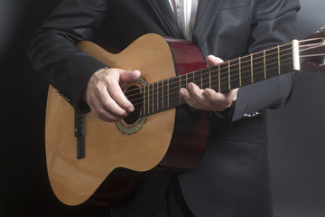 Man in black suit with acoustic classic guitar