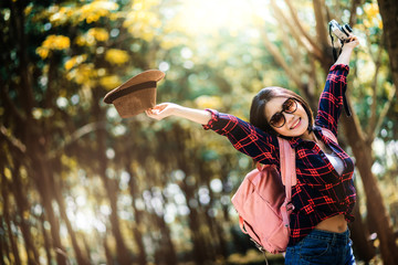 beautiful travel asian woman enjoy walking and take photo with vintage camera in camping forest background with joyful and happiness