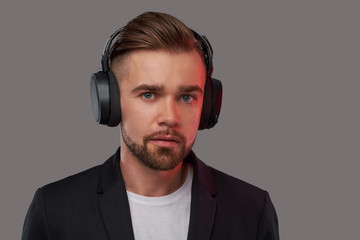 Close-up portrait of a stylish bearded man with hairstyle listening to music in headphones.