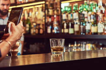 Cropped image of a customer of the bar takes a picture on the phone of a glass of alcohol on a bar counter.