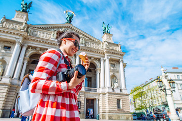 tourist woman with photo camera and ice cream in the middle of european city