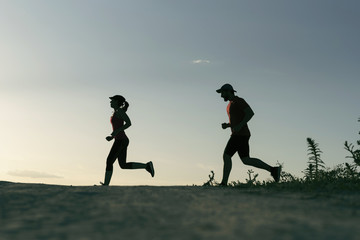 A couple of runners training on road in sunset