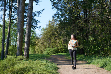 young girl walking in spring forest with camera and taking pictures