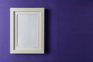 Minimalism style. White empty picture frame against; abstract colored paper background; flat lay
