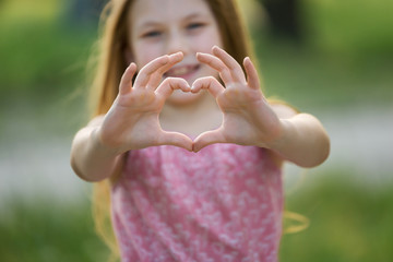 Pretty little girl shows heart shaped gesture