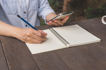 Hand woman write notebook and holding phone on wood table.