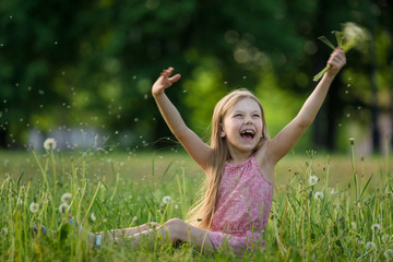 A girl sits on the grass and plays with dandelions