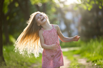 Little girl is shaking hair outdoor