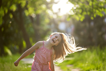 Joyfull little girl is shaking hair outdoor. Summer childhood