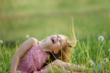 Cute happy girl plays in the garden. Baby has fun on the fresh grass