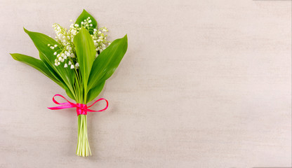 bouquet of lily of the valley flowers tied with a red ribbon on a gray wooden background with copy space