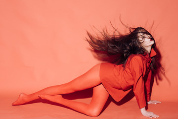 Lady waving her hair while sits on floor. Woman with stylish makeup and long hair posing in total red outfit. Fashion concept. Girl on mysterious face in red formal jacket and tights, red background.