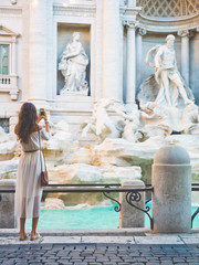 Woman in white dress  in front of Trevi Fountain in Rome