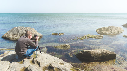 Man takes picture on the phone mounted on a tripod on a sea rocky coast