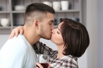 Happy young couple kissing in kitchen