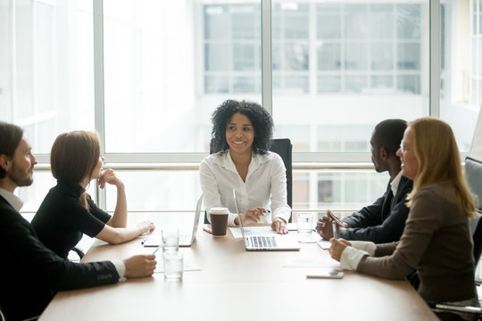 Smiling friendly african female boss leading corporate diverse team meeting talking to multiracial partners employees discussing results or planning work at group multi-ethnic briefing in boardroom