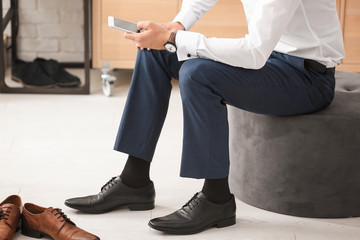 Man using smartphone while trying on new shoes indoors