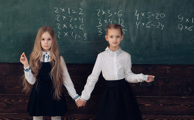 Educational concept - schoolchildren in a classroom. Enrichment classes can be difficult for some kids so tutors are best. Final exam test in university students study for examination in classroom.