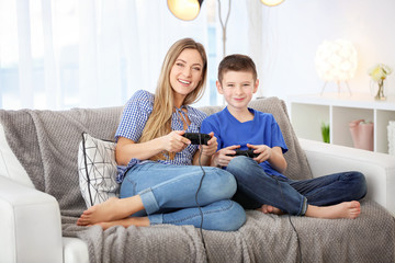 Young woman playing video games with her son at home