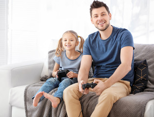 Young man playing video games with his daughter at home